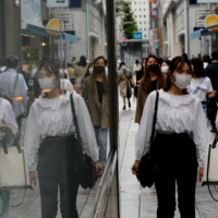 People wearing protective masks make their way at a shopping district in Tokyo this month.  | REUTERS