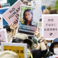 People opposing the revision of Japan's immigration control and refugee recognition law march in Tokyo on May 16. Many held up photos of Ratnayake Liyanage Wishma Sandamali, who died while being held at the Nagoya Regional Immigration Services Bureau. | KYODO