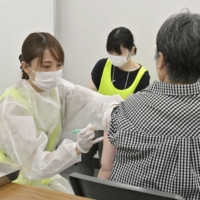 Playing it safe: A woman in Osaka gets a dose of the AstraZeneca vaccine to protect against COVID-19. | KYODO
