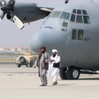 Taliban members walk in front of a military airplane at Kabul airport a day after U.S. troops withdrew from the country.    REUTERS