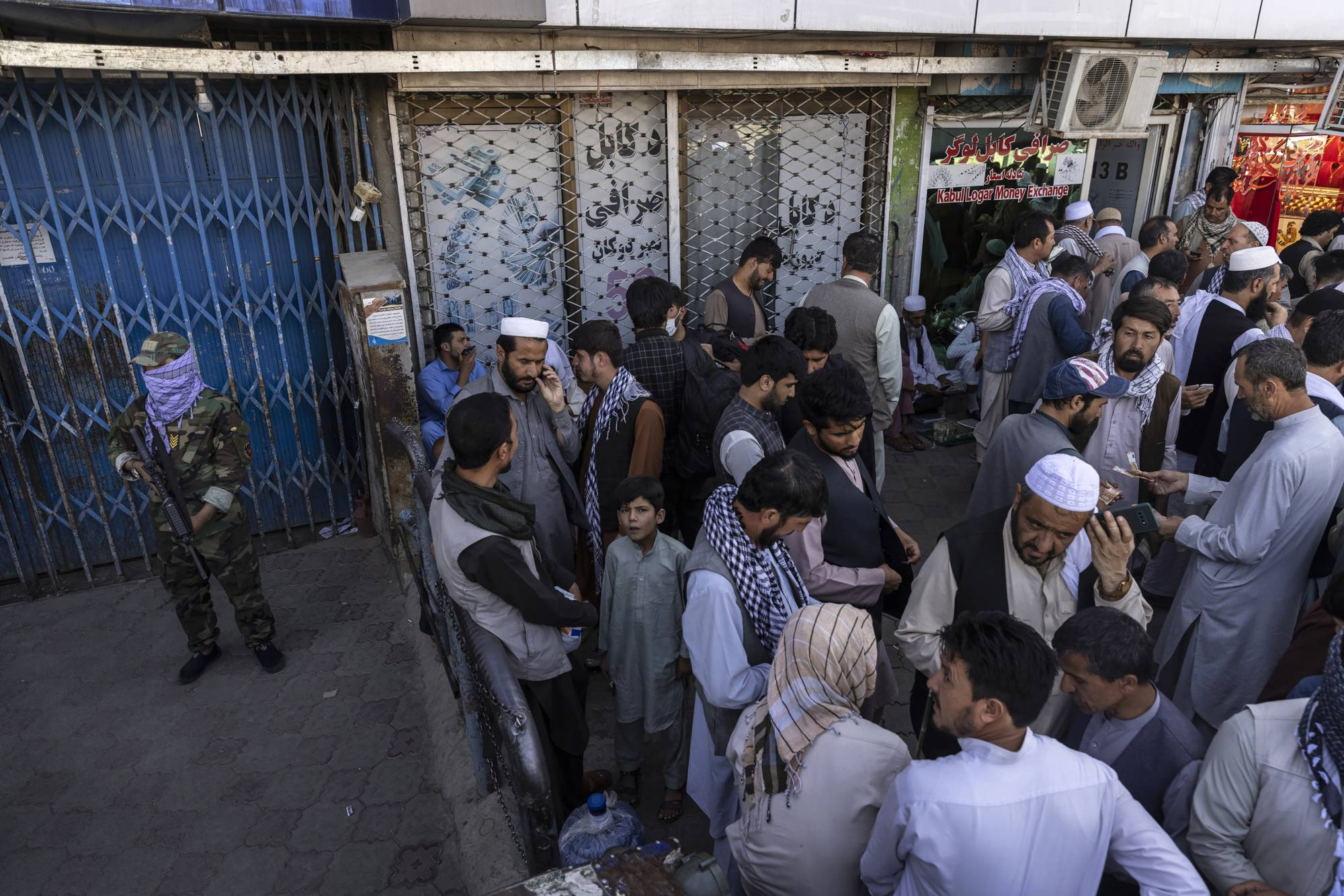 Crowds outside a currency exchange facility in Kabul on Aug. 26 as Taliban fighters stand guard   VICTOR J. BLUE / THE NEW YORK TIMES