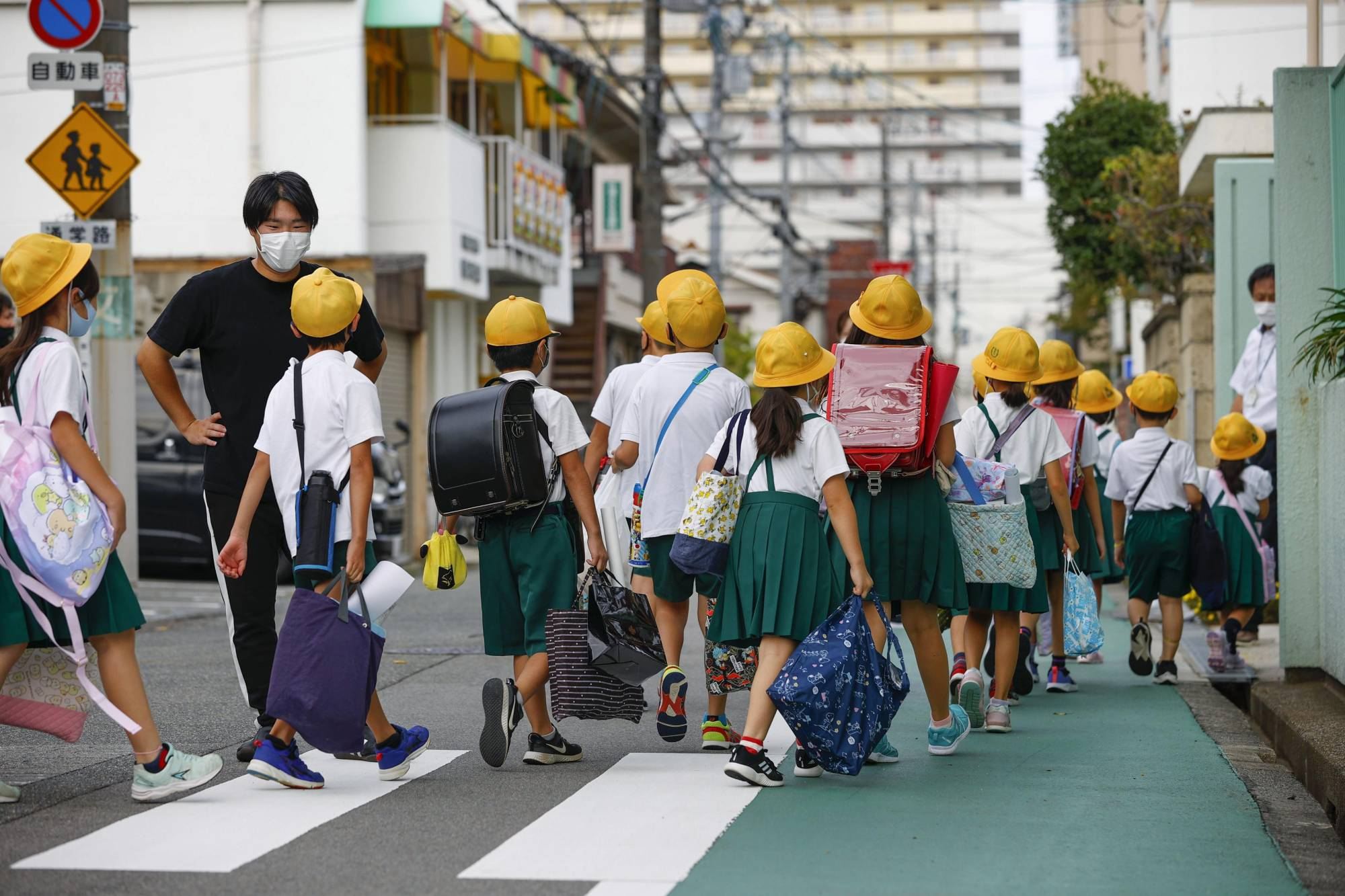Students arrive at an elementary school in the city of Osaka on Aug. 25, the first day of the new semester.   KYODO