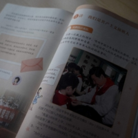 A primary school textbook featuring a photograph and quotes from Chinese President Xi Jinping is displayed on Tuesday.  | AFP-JIJI
