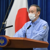 Prime Minister Yoshihide Suga speaks to reporters during a drill for a potential earthquake striking directly under Tokyo on Wednesday.   KYODO