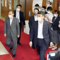 Prime Minister Yoshihide Suga leaves the Liberal Democratic Party headquarters in Tokyo on Thursday after holding talks with LDP Secretary-General Toshihiro Nikai. | KYODO