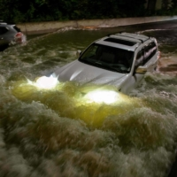A motorist drives a car through a flooded expressway in Brooklyn, New York early Thursday as flash flooding and record-breaking rainfall brought by the remnants of Storm Ida swept through the area. | AFP-JIJI