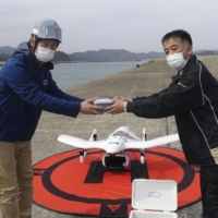 A municipal official (right) of Goto, Nagasaki Prefecture, receives a package containing a blood sample delivered by a test flight of ANA Holdings Inc.'s drone in March. | ANA HOLDINGS INC. / VIA KYODO