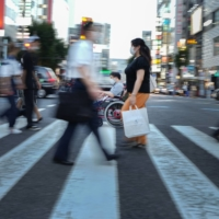 Yuto Hirano, a volunteer for the Paralympics, rolls through a crosswalk on his way to a haircut appointment in Tokyo on Aug. 23. Tokyo improved its infrastructure before the delayed 2020 Games, but activists wonder how long the focus will continue in a country with a long history of excluding people with disabilities.  | CHANG W. LEE/THE NEW YORK TIMES