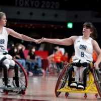 Britain's Robyn Love (left) and her partner Laurie Williams touch hands during their match against Spain on Thursday.    AFP-JIJI