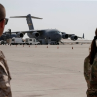 U.S. military officers stand near U.S. Air Force planes, which were used to evacuate people from Afghanistan, at Al Udeid airbase in Doha on Saturday.  | REUTERS