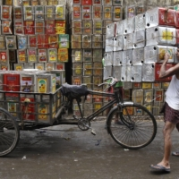 A man loads empty containers of edible oil onto a tricycle in Kolkata.   REUTERS