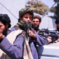 Taliban forces stand guard in front of Hamid Karzai International Airport in Kabul on Thursday.    | REUTERS