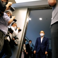 Prime Minister Yoshihide Suga arrives to meet with Andrew Parsons, president of the International Paralympic Committee, in Tokyo on Friday. | POOL / VIA REUTERS