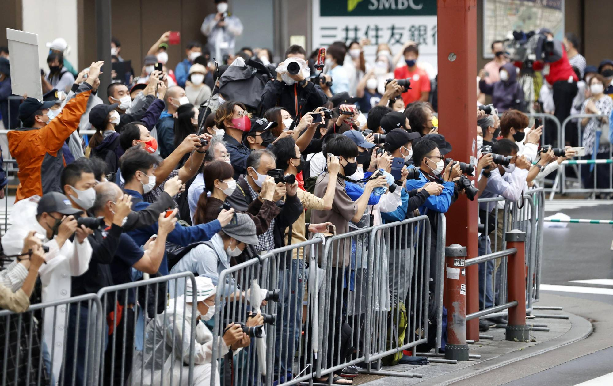 People gather in Tokyo's Asakusa district on Sunday to watch the Paralympics marathon.   KYODO