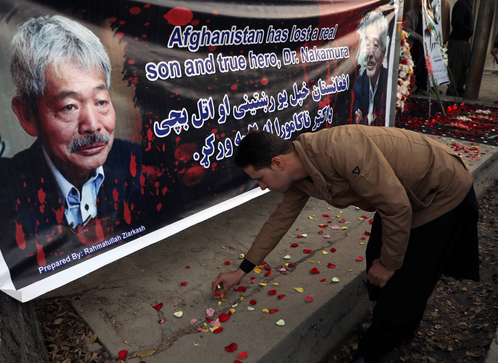 A man lights candles for Japanese doctor Tetsu Nakamura in Kabul days after he was killed in an attack Jalalabad in December 2019.   REUTERS