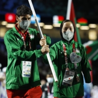 Afghan athletes Hossain Rasouli (left) and Zakia Khudadadi carry their nation's flag into the stadium during the closing ceremony. | REUTERS