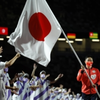 Table tennis player Koyo Iwabuchi carries the Japanese flag during the closing ceremony. | REUTERS