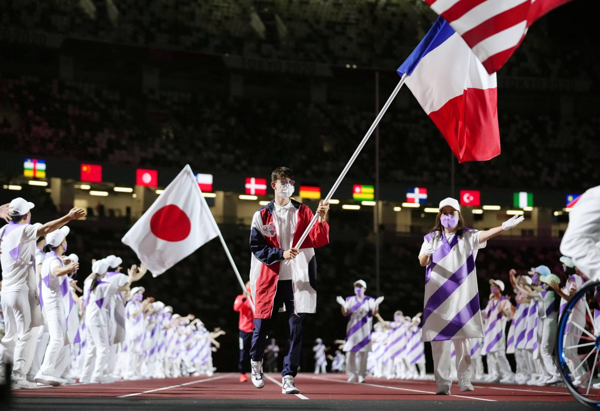 The French delegation's flag bearer enters the National Statdium ahead of Japan's flag bearer. | KYODO