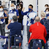 Volunteers see off Paralympic athletes who are returning home via Tokyo's Haneda airport on Monday.   KYODO