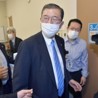Former Defense Minister Shigeru Ishiba leaves his faction's meeting at the Diet on Tuesday. | KYODO