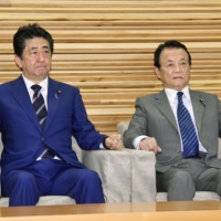 Shinzo Abe and Taro Aso, both former prime ministers, hold an enviable level of sway behind the scenes of the Liberal Democratic Party. | KYODO