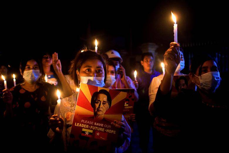People hold candles during a nationwide vigil against the military coup in Mandalay, Myanmar March 12, 2021.  | REUTERS