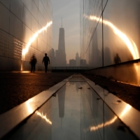A man walks through a memorial for the victims of the terrorist attacks attacks on Sept. 11, 2001, at sunrise across from New York's Lower Manhattan and the One World Trade Center. | GARY HERSHORN / REUTERS