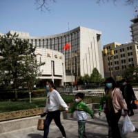 People walk past the headquarters of the People's Bank of China in April 2020. Chinese authorities have signaled a further cut in the reserve requirement for lenders after July's reduction.  | REUTERS