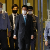 Lower House lawmaker Tsukasa Akimoto (center) leaves the Tokyo Detention House on Tuesday after being released on bail.   KYODO