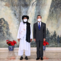 Mullah Abdul Ghani Baradar meets with Chinese State Councilor and Foreign Minister Wang Yi in Tianjin, China, in July. | XINHUA / VIA REUTERS