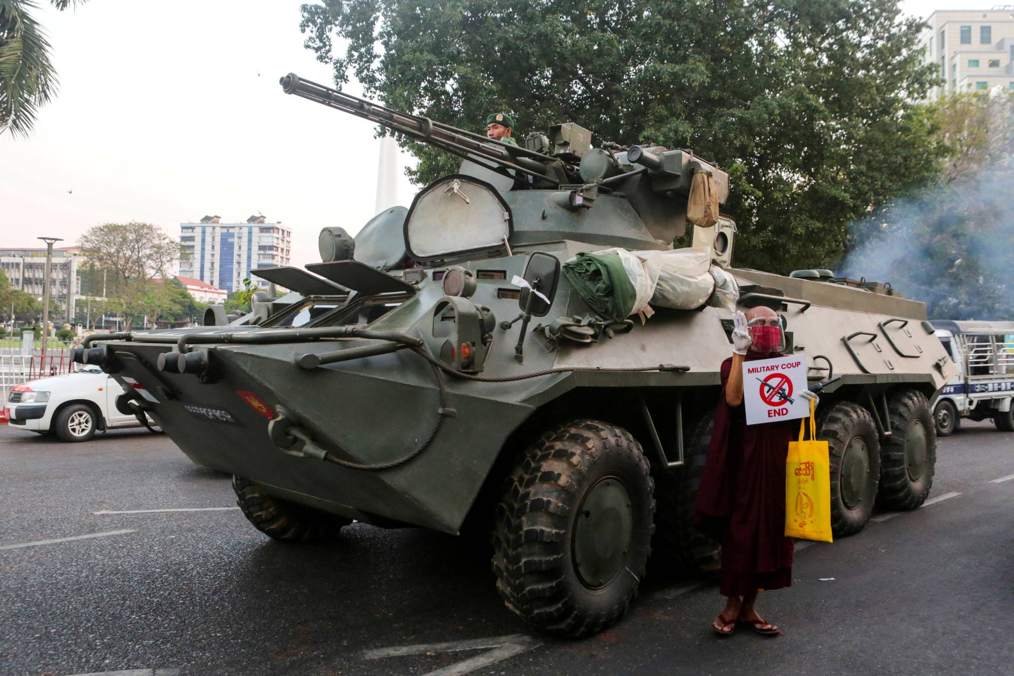 A Buddhist monk stands next to a tank during a protest against the military coup on Feb. 14. | REUTERS