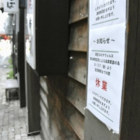 A temporarily closed sign hangs on a shop door in Asahikawa, Hokkaido, on Aug. 27 as the prefecture came under a coronavirus state of emergency. | KYODO