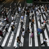 People walk in the city of Osaka's Umeda district last week. The Osaka Prefectural Government said Wednesday that a teenage boy with COVID-19 has died in the prefecture, in what is believed to be the first coronavirus-linked death among people under 20 in the country. | KYODO