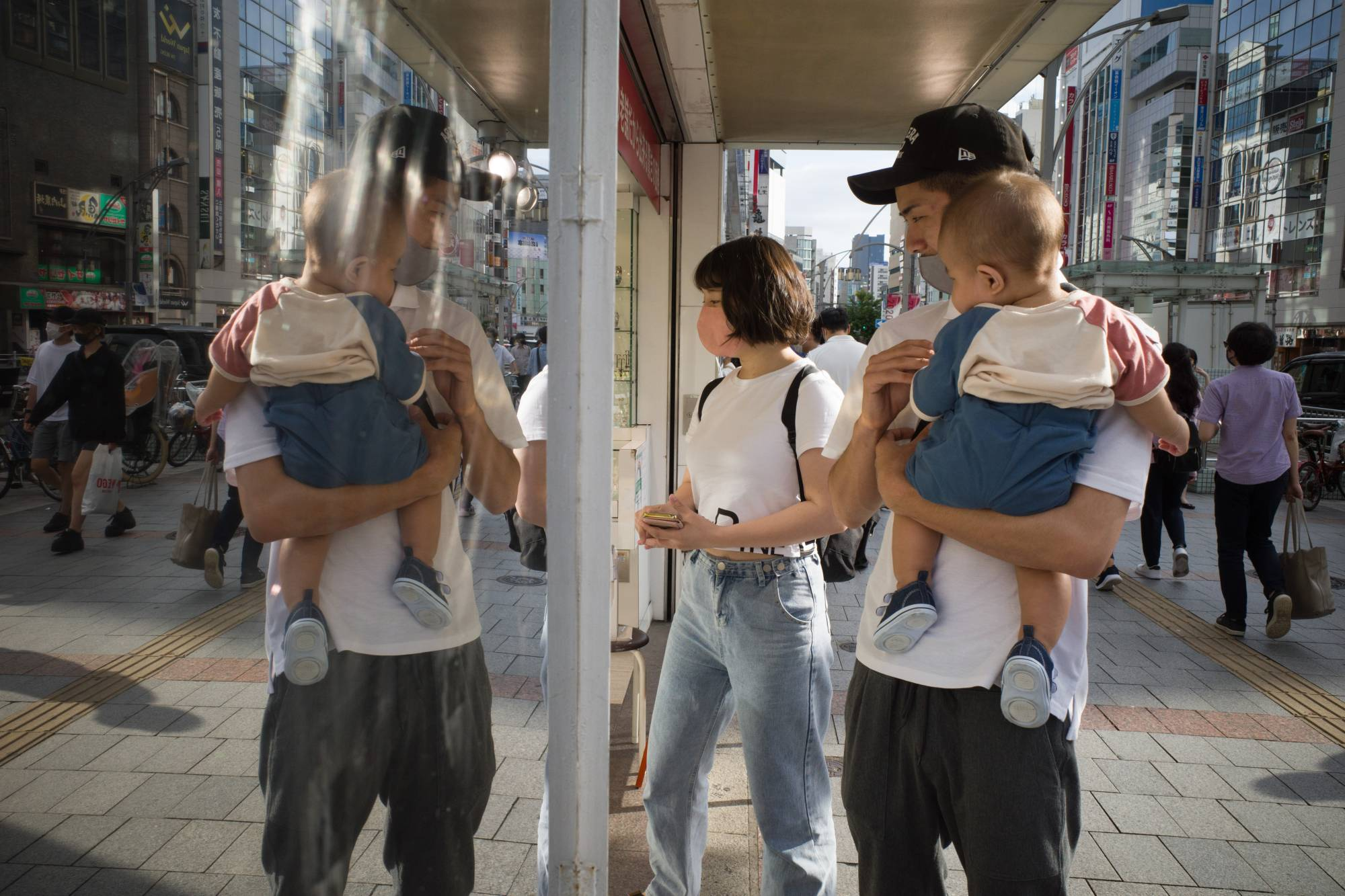 A young family on the Ameyoko shopping street in Tokyo on Sunday | BLOOMBERG