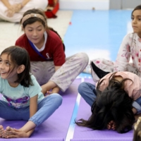 Refugee children from Afghanistan during a yoga session in Doha on Tuesday.    MINISTRY OF FOREIGN AFFAIRS OF QATAR / VIA AFP-JIJI