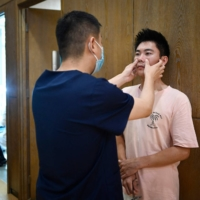 A doctor examines Xia Shurong a week after his plastic surgery at a clinic in Beijing.    AFP-JIJI