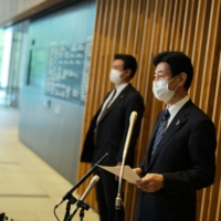 Yasutoshi Nishimura, the minister leading the country's pandemic response, speaks to reporters in Tokyo on Thursday. | RYUSEI TAKAHASHI