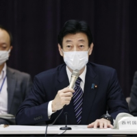Yasutoshi Nishimura, minister in charge of Japan's coronavirus response, speaks at a government panel meeting on COVID-19 measures Thursday. | KYODO