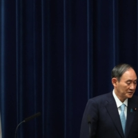 Prime Minister Yoshihide Suga leaves after a news conference at his office in Tokyo on Thursday.   AFP-JIJI