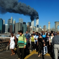 Pedestrians walk across Brooklyn Bridge away from the burning World Trade Center towers before their collapse on Sept. 11, 2001.   AFP-JIJI