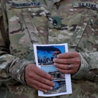 A U.S. soldier holds photographs of the 9/11 attacks during a ceremony marking the 13th anniversary of 9/11 at the Bagram airbase north of Kabul on Sept. 11, 2014.   REUTERS