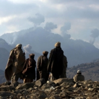Anti-Taliban Afghan fighters watch explosions from U.S. bombings in the Tora Bora mountains in Afghanistan on Dec. 16, 2001.   REUTERS