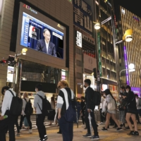 A big screen in Tokyo's Shinjuku district Thursday shows Prime Minister Yoshihide Suga announcing an extension to a state of emergency in 19 prefectures.   KYODO