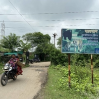 A signboard cautions residents to stay alert to wildlife movement outside Khairgaon village in Chandrapur, India, in August. | THOMSON REUTERS FOUNDATION