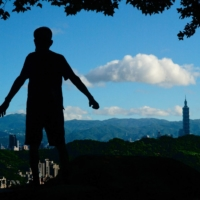 A man exercises in front of Taipei 101, a 508-meter high commercial building, in the Taiwanese capital on Aug. 31. | AFP-JIJI