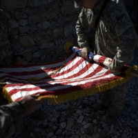 U.S. soldiers take down a flag after a memorial service for a fallen comrade in Afghanistan's Kunar province in April 2009.    TYLER HICKS / THE NEW YORK TIMES