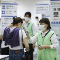 A staffer checks the temperature of a woman at a vaccination center in Nagoya on Saturday.   KYODO