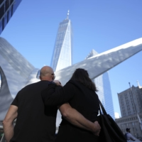 Visitors look up at One World Trade Center in New York on Saturday.  | CHANG W. LEE/THE NEW YORK TIMES