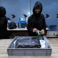 Afghan women who work at Kabul airport at a security checkpoint on Sunday.  | AFP-JIJI
