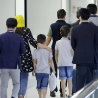 Passengers who are believed to be Afghan evacuees (second from left to fifth from left) arrive at Narita Airport on Sunday evening. | KYODO